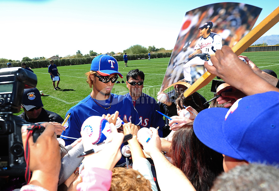 Mar. 1, 2012; Surprise, AZ, USA; Texas Rangers pitcher Yu Darvish signs autographs for fans during spring training workouts at the practice fields at Surprise Stadium.  Mandatory Credit: Mark J. Rebilas-.