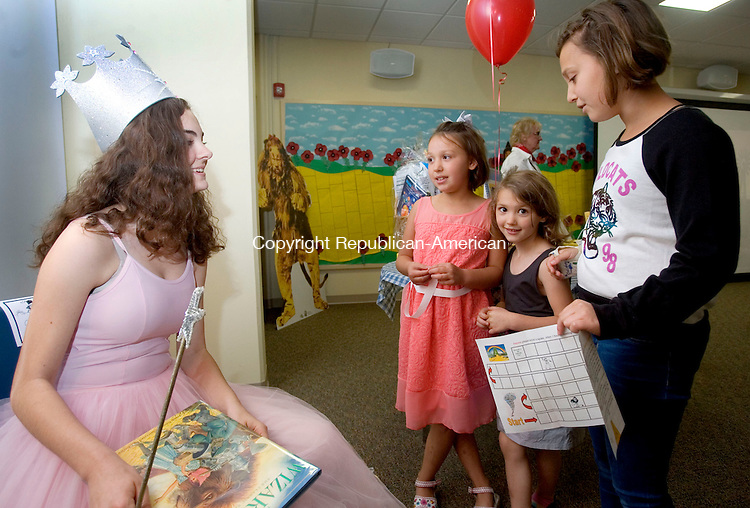 MIDDLEBURY CT. 01 June 2015-060115SV08-From left, Deanna Pietrorazio, 15, of Middlebury, dressed as Gilda the good witch, talks with Savannah Fedorich, 7, and her sisters Gabirella, 5, and Mikayla, 11, all of Middlebury about the summer reading program at the library in Middlebury Monday. The library was having their annual summer reading kickoff.  <br /> Steven Valenti Republican-American