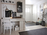 A small workspace is arranged in a corner of the hallway. The old family furniture gives the clean white space of the 1970s wing a richer patina