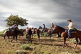 USA, Wyoming, Encampment, wranglers take horses from guests after a ride, Abara Ranch
