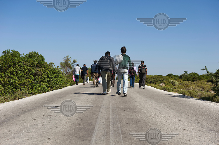 A group of Afghan refugees walk along the road between Mantamado and Mytilini. Most refugees land on the northern shores of the island and walk for nine hours either to Mytilini port or to Moria First Reception Centre. Every day hundreds of refugees, mainly from Syria and Afghanistan, are crossing in small overcrowded inflatable boats the six mile channel from the Turkish coast to the island of Lesbos in Greece. Many spend their life savings, over $1,000, to buy a space on these boats.