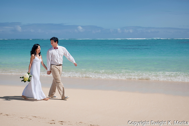 Asian bride and groom stroll on Lanikai beach as they look forward to their life as a married couple following their wedding.