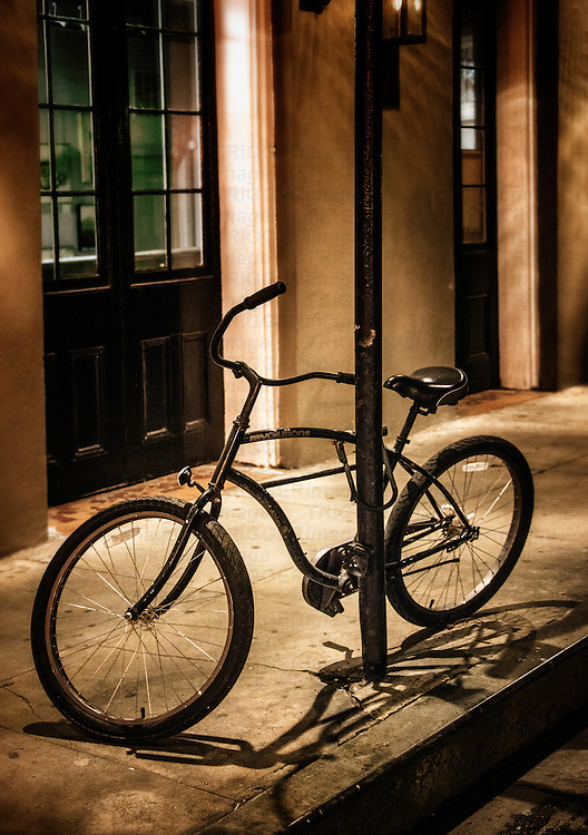 A bike chained to a street post with shadows in America