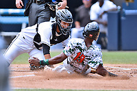 Asheville Tourists catcher Joel Diaz (5) fields and tags out a hard sliding Ashford Fulmer (19) as Matthew Brown prepares to make the call during a game against the Augusta GreenJackets at McCormick Field on July 16, 2017 in Asheville, North Carolina. The GreenJackets defeated the Tourists 10-9. (Tony Farlow/Four Seam Images)
