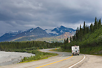 Motorhome travels the Richardson Highway along the delta river in the Alaska mountain range.