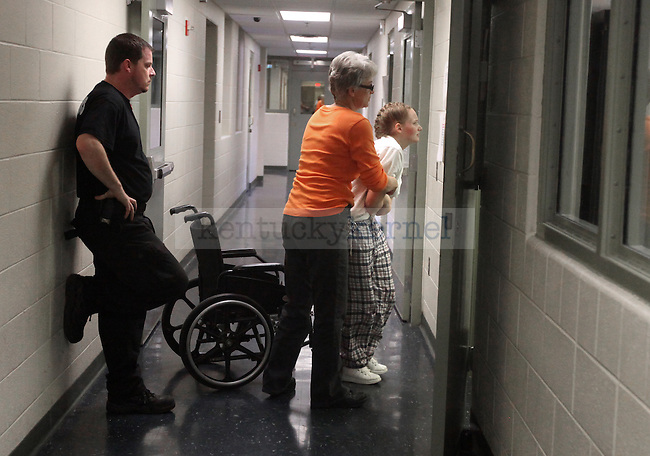 """""""Girl, you are never gonna see the light of day again,"""" officer Mikey Allen said Mikey Allen, who stands guard while Rebbeca Cobin takes Driggers into the nurses station at Three Forks Regional Jail. Photo by Britney McIntosh"""