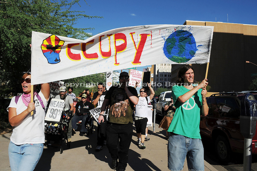"Phoenix, Arizona. September 17, 2012 - A small crowd of demonstrators in Phoenix, Arizona gathered to mark one year since the beginning of the Occupy Movement that opposes Wall Street and large corporations that represent the one percent who control wealth in the United States. In this photograph, Occupy Phoenix activists Rachel Skaggs (left) and Michael Nehl Royeran (right) hold an ""Occupy"" banner as they lead the march on Jefferson Street in Downtown Phoenix. Activists marked the first anniversary of the Occupy Wall Street Movement. Photo by Eduardo Barraza © 2012"