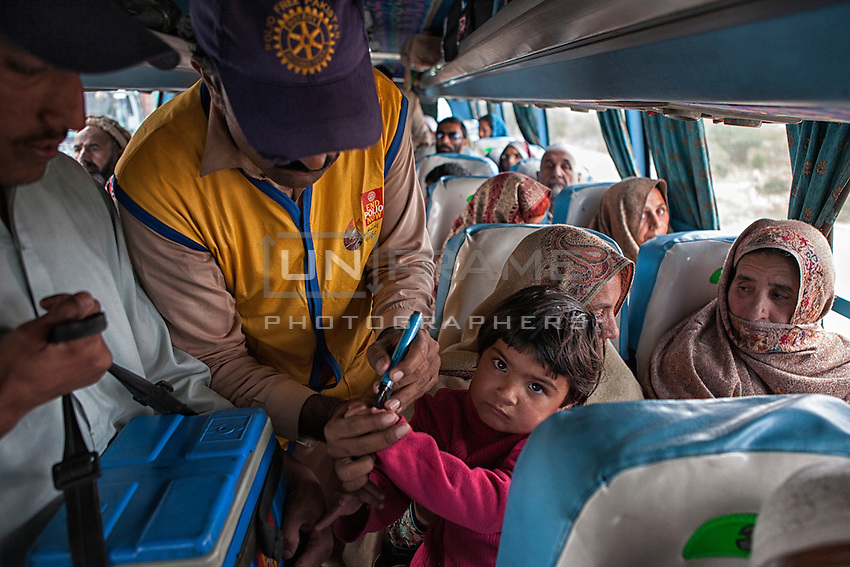 A Pakistani health worker administers polio drops to children aboard buses arriving in Karachi city from other provinces at the transit point in Karachi, Pakistan on Jan. 08, 2014