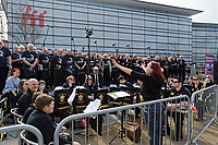 Pictured: A local choir performs at The Man Engine show at the Waterfront Museum in Swansea, Wales, UK. Thursday 12 April 2018<br /> Re: The largest mechanical puppet in Britain starts its tour across south Wales.<br /> Man Engine, a mechanical miner which measures 36ft (11m) tall, will appear at the Waterfront Museum in Swansea, Wales, animated by a dozen handlers.<br /> The giant is visiting areas linked to the nation's industrial past.