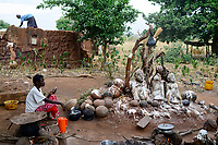 BURKINA FASO , Gaoua, Kampti, Lobi culture, Lobi is an ethnic group and they are animist and worship ancestor spirit, village KWEKWERA ( KOUEKOUERA ), court of fetish maker DA LEPIRTHE, fetish figure made from clay, woman with mobile phone / Lobi Ethnie, Lobi sind Animisten und praktizieren Ahnenkulte, Dorf KWEKWERA ( KOUEKOUERA ), am Hof des Fetischmeister DA LEPIRTHE, Fetisch Figur aus Lehm, Frau mit Mobiltelefon
