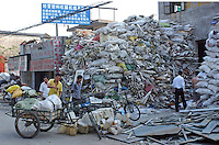 Men unload rubbish from trucks on the road of an area of Nanhai that specialises in the re-cycling of rubbish.