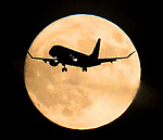 An airline jet flies through the center of October's full moon on its approach landing at SFO.