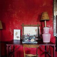 Various items, including a pink ceramic vase and a lamp, are displayed on a pink metal table, which stands against a vibrant red painted wall. A simple wood chair is set in front of the table.