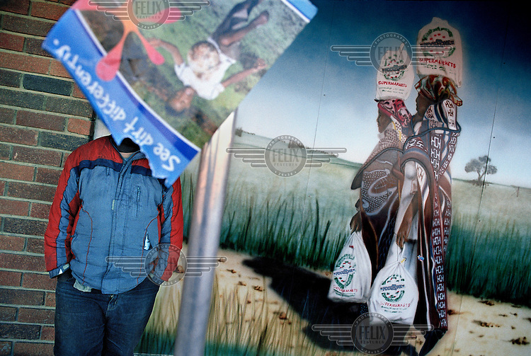 A man stands next to a mural of women carrying shopping bags in Marquard.