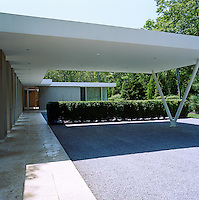 A cantilevered awning, at the end of the path leading to the house, provides shelter for cars