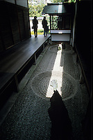A pair of visitors hesitate for a moment while a sumbeam illuminates a Zen garden vignette in one of the sub temples at the Diatokuji temple complex in Kyoto.