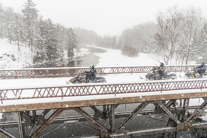 Snowmobiles cross the Dead River near Marquette, Michigan.