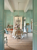 A view through a pair of open double doors into a traditional reception room decorated in turquoise blue. Cane back chairs are placed around a round table. The colour scheme and furniture lends the room a Scandinavian feel.