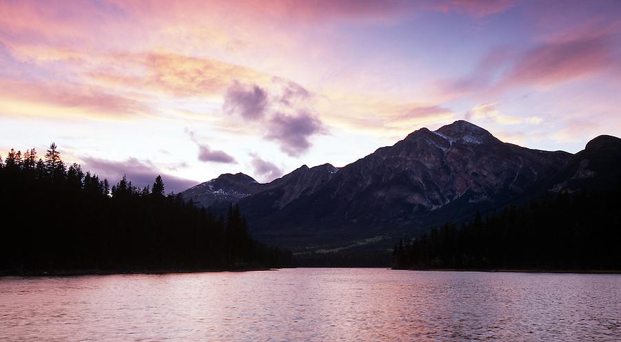 Pink, orange, and purple lit clouds shine around Pyramid Mountain in Jasper National Park in Alberta, Canada.