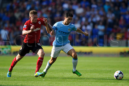 25.08.2013 Cardiff, Wales. Cardiff Midfielder Aron Gunnarsson and Man City Midfielder Samir Nasri compete for the ball during the second half of the Barclays Premier League football match between Cardiff City and Manchester City at Cardiff City Stadium.