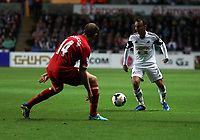 Pictured: Leon Britton of Swansea (R) against Jordan Henderson of Liverpooll (L)<br /> Monday 16 September 2013<br /> Re: Barclay's Premier League, Swansea City FC v Liverpool at the Liberty Stadium, south Wales.