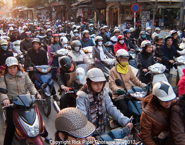 Hanoi Rush Hour - Late afternoon rush hour motorbike traffic in Hang Gai St, Hanoi Old Quarter, Vietnam