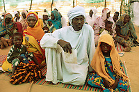 Sudan. West Darfur. Kerenek. The non-governmental organization (ngo) Médecins sans Frontières (MSF) Switzerland runs a medical program. A group of men, women and children, seated on the groung, wait for a medical consultation with a doctor. The women wear a veil on their heads, the men a turban. © 2004 Didier Ruef