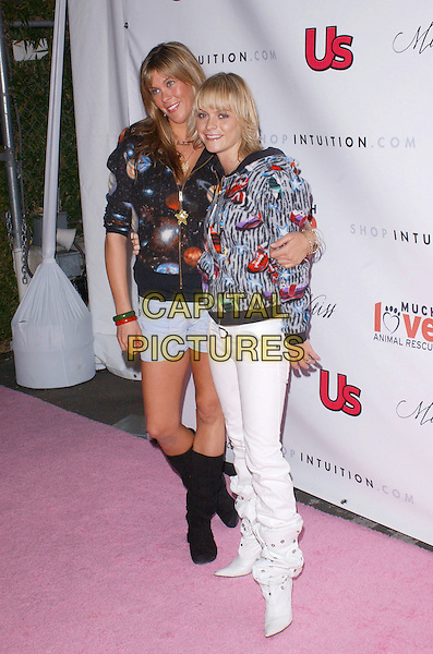TARA JANE & TARYN MANNING.The 1st Annual US Weekly Hollywood Holiday Shopping Party hosted by US Weekly Magazine and Tori Spelling at Smashbox Studios..November 11th, 2004.full length, zip  up printed pattern jackets coats white jeans white boots, arm around waist.www.capitalpictures.com.sales@capitalpictures.com.© Capital Pictures.