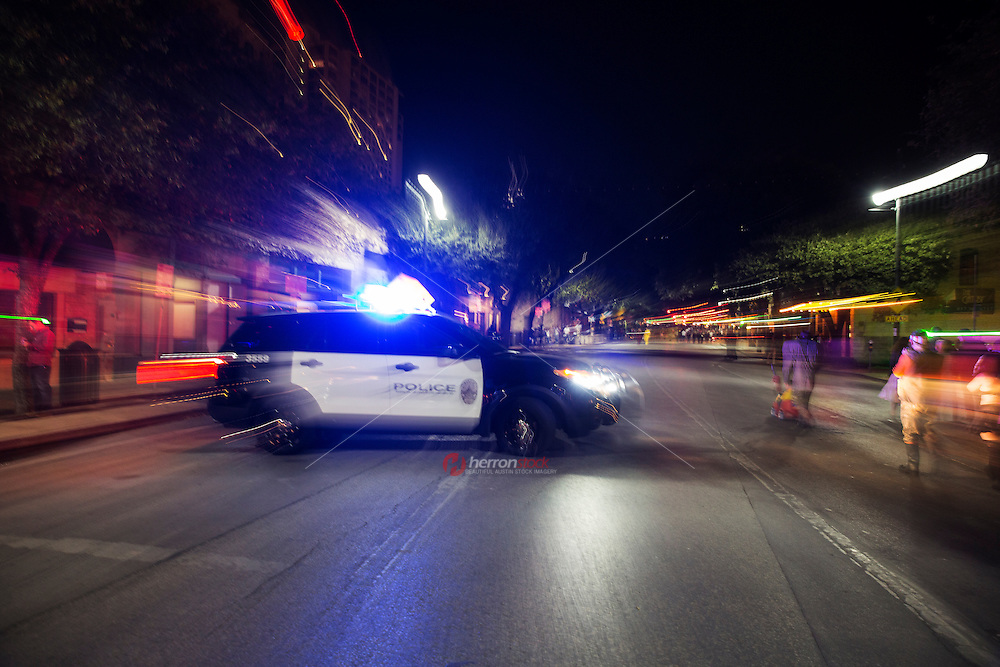 Austin Police car on the street at night with flashing tactical and emergency lights.<br />