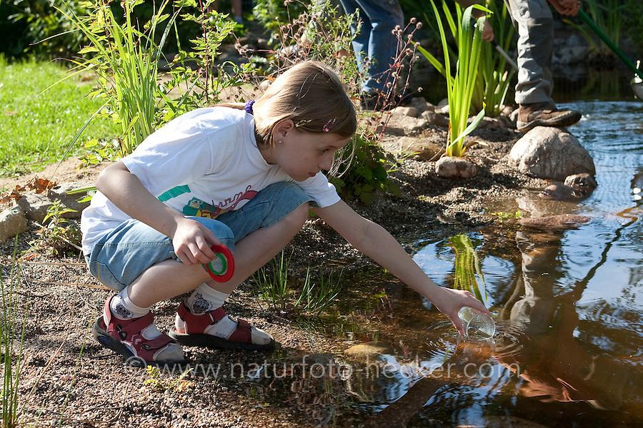 Grundschulklasse, Schulklasse im Schulgarten an ihrem selbst angelegtem Schulteich, Schul-Teich, Gartenteich, Garten-Teich, Mädchen nimmt Wasserprobe aus Teich, Exkursion am Teich, Biologie-Unterricht im Freien, Grünes Klassenzimmer