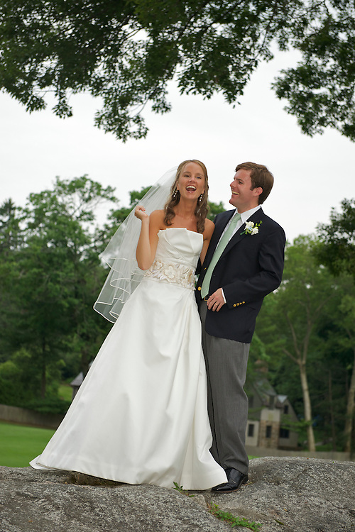 Full length shot of bride and groom standing on top of a boulder with the golf course in the background.