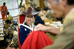 "Leo Shigeta, 16, is given a helping hand by Akimasa Matsumoto to put on traditional attire prior to the ""yabusame-shinji"" horseback archery ritual on the final day of the Reitaisai grand festival at Tsurugaoka Hachimangu shrine in Kamakura, Japan on  14 Sept. 2012. The yabusame ritual is performed by members of the Ogasawara school, which began mounted archery rituals in the 12th century. .Yabusame was originated in middle of 6th century as a Shinto ritual. Today there are various styles and manners of Yabusame inherited by different shrines and particular families. It was common in the ancient past that the result of Yabusame depended on the number of targets successfully hit, and also fragments of the target were used to tell fortunes. The target and arrows used in successful shots were kept as amulets. The initiation of Yabusame in Tsurugaoka Hachimangu was 1186. Photographer: Robert Gilhooly"