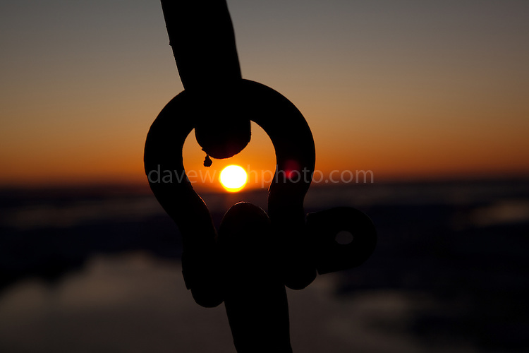 Sunset through a shackle on board the Greenpeace ship Arctic Sunrise, amidst the Arctic Sea Ice, Fram Strait, between Greenland and Svalbard, September 2009. In August 2012, Arctic sea ice hit a record minimum - this will affect weather and the global climate, as the ice cap reflects much of the sun's solar energy back into to space. With sea ice melting away, the dark water below absorbs more solar energy, which in turn causes more melting.