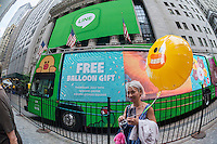 """Hordes of visitors clammer for free balloons with faces representing Line """"stickers"""" in front of the New York Stock Exchange decorated for the Japanese messaging company Line's initial public offering on Thursday, July 14, 2016. Line Corp., a popular messaging app in Japan is owned by South Korean Naver Corp. Line has 218 million active users monthly, with Japan, Taiwan and Indonesia accounting for two-thirds of them.   (© Richard B. Levine)"""