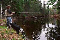 A MAN FLY FISHES WITH HIS DOG ON THE EAST BRANCH OF THE ESCANABA RIVER NEAR GWINN MICHIGAN.