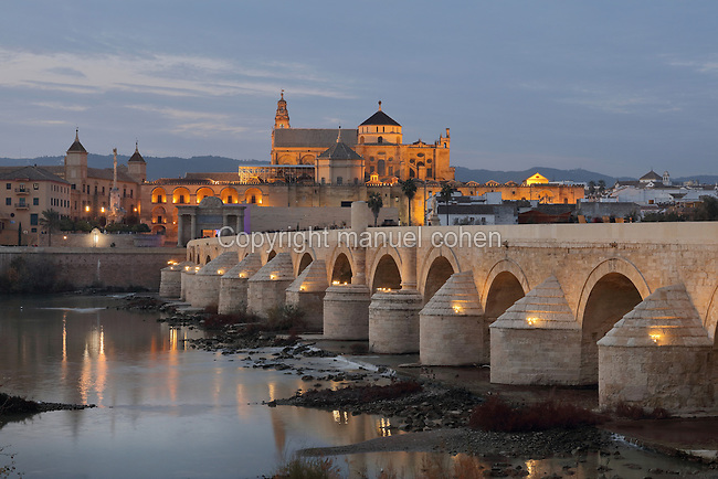 The Roman bridge, built 1st century BC over the Guadalquivir river, and behind, the Cathedral-Great Mosque of Cordoba, in Cordoba, Andalusia, Southern Spain. The first church built here by the Visigoths in the 7th century was split in half by the Moors, becoming half church, half mosque. In 784, the Great Mosque of Cordoba was built in its place, but in 1236 it was converted into a catholic church, with a Renaissance cathedral nave built in the 16th century. The historic centre of Cordoba is listed as a UNESCO World Heritage Site. Picture by Manuel Cohen