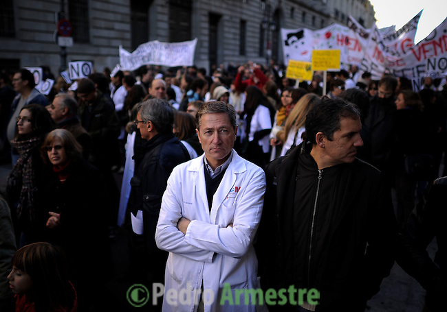 """Medical workers take part in a demonstration against plans to cut medical spending and privatise hospital services, in Madrid onDecember 09, 2012. The Madrid regional government plans to privatise six hospitals and 27 health centres of the 270 in the region. Placard reads """"Health 100x100 public. (c) Pedro ARMESTRE"""