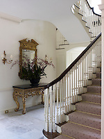 A grand staircase sweeps down into the central stone flagged entrance hall