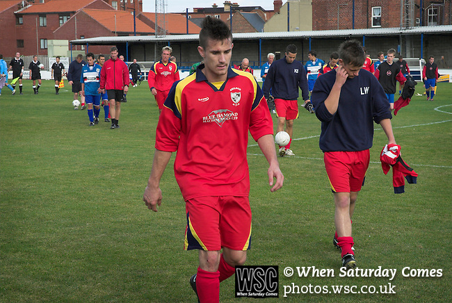 A dejected Shildon player leaves the pitch at full time.