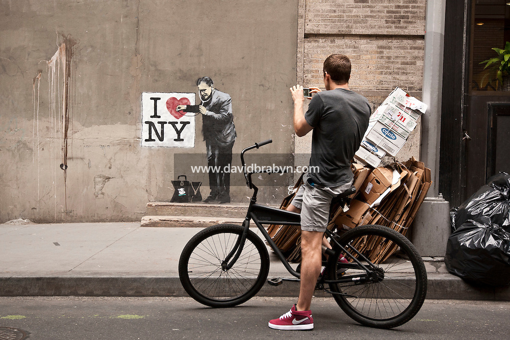 "A man photographs work that appears to be by incognito street graffiti artist Banksy on a wall near Ground Zero and Wall Street in New York, USA, 17 May 2010. The British artist is said to be in New York to promote his movie about street art, ""Exit Through the Gift Shop"". Several pieces of artwork have been sighted around the city today."