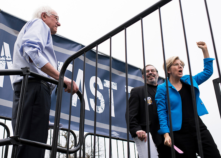UNITED STATES - APRIL 15: Sen. Bernie Sanders, I-Vt., left, waits to speak as Sen. Elizabeth Warren, D-Mass., right, wraps up her speech during the United Steelworkers rally in opposition to the proposed 'Fast Track' bill, or Trade Promotion Authority, in UpperSenate Park on Wednesday, April 15, 2015. United Steelworkers president Leo Gerard is pictured center. (Photo By Bill Clark/CQ Roll Call)