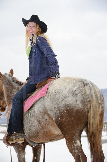 Pretty blonde woman riding her Appaloosa horse, a happy twenty-something in casual western wear with black cowboy hat, rear view looking over shoulder, winter outdoors in snow, Pennsylvania, PA, USA.