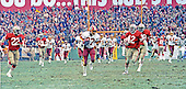 Washington, D.C. - January 8, 1984 -- Washington Redskins wide receiver Charlie Brown (87) runs with the ball after catching a pass from quarterback Joe Theismann (7) late in the third quarter in the NFC Championship game at RFK Stadium in Washington, D.C.  In pursuit are 49ers free safety Dwight Hicks (22) and left cornerback Ronnie Lott (42).  Brown scored the Redskins third touchdown on the 70 yard play.   The Redskins won the game 24 - 21 to go to Super Bowl XVIII.<br /> Credit: Howard L. Sachs / CNP