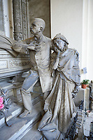 Picture and image of the stone sculpture of a grieving family around the death bed of the deceased. In a Borgeoise realistic style sculpted by GB Villa 1896. The Rivara Family Tomb, Section D no 15, the monumental tombs of the Staglieno Monumental Cemetery, Genoa, Italy