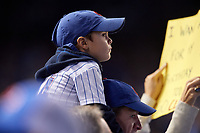A young Chicago Cubs fan sits on his fathers shoulders to watch the action in the first inning during Game 4 of the Major League Baseball World Series against the Cleveland Indians on October 29, 2016 at Wrigley Field in Chicago, Illinois.  (Mike Janes/Four Seam Images)