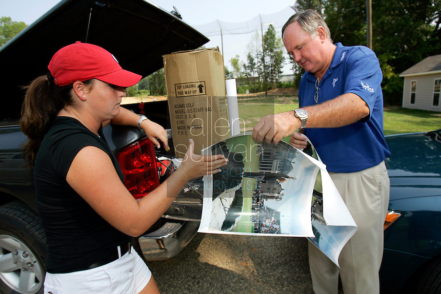 PGA Senior Tour player Allen Doyle hands a signed poster of Arnold Palmer to his youngest daughter, Michelle Griffith, at The First Tee of Troup County in LaGrange, Ga. on Wednesday, August 2, 2006. Griffith said the print will be sold at auction to help fund the nine-hole The First Tee course, a cooperative effort between golfers like Doyle's family, the Troup County recreation department and donors..