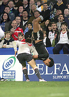 New Zealand centre Robert Fruean flies through the air as he slips out of the tackle off Welsh replacement Tom Williams in the Division A semi final at Ravenhill.