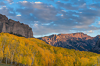 Uncompahgre National Forest, Colorado:<br /> Cliffs of the Cimarron stand abouve fall colored hillsides in evening, sunset, light, San Juan Mountains