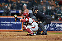 Arkansas Razorbacks catcher Casey Opitz (12) sets a target as home plate umpire Ryan Morehead looks on during the game against the Texas Longhorns in game six of the 2020 Shriners Hospitals for Children College Classic at Minute Maid Park on February 28, 2020 in Houston, Texas. The Longhorns defeated the Razorbacks 8-7. (Brian Westerholt/Four Seam Images)