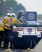 Jun 2, 2018; Joliet, IL, USA; NHRA funny car driver John Force is helped from his car by the Safety Safari safety team after crashing into the wall during qualifying for the Route 66 Nationals at Route 66 Raceway. Force would walk away from the crash. Mandatory Credit: Mark J. Rebilas-USA TODAY Sports